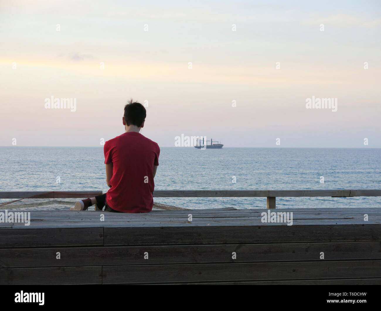 Young man sitting alone at the promenade looking at ship anchored off the coast, listening to music, ( concept of loneliness, relaxation). Stock Photo