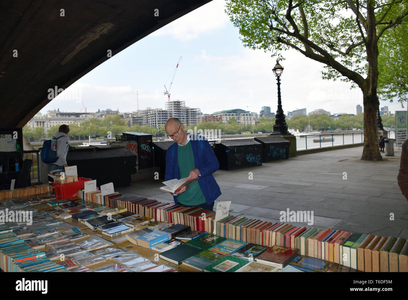 Second hand book stall on South Bank, London UK April 2019. Posed by model - Stock Image
