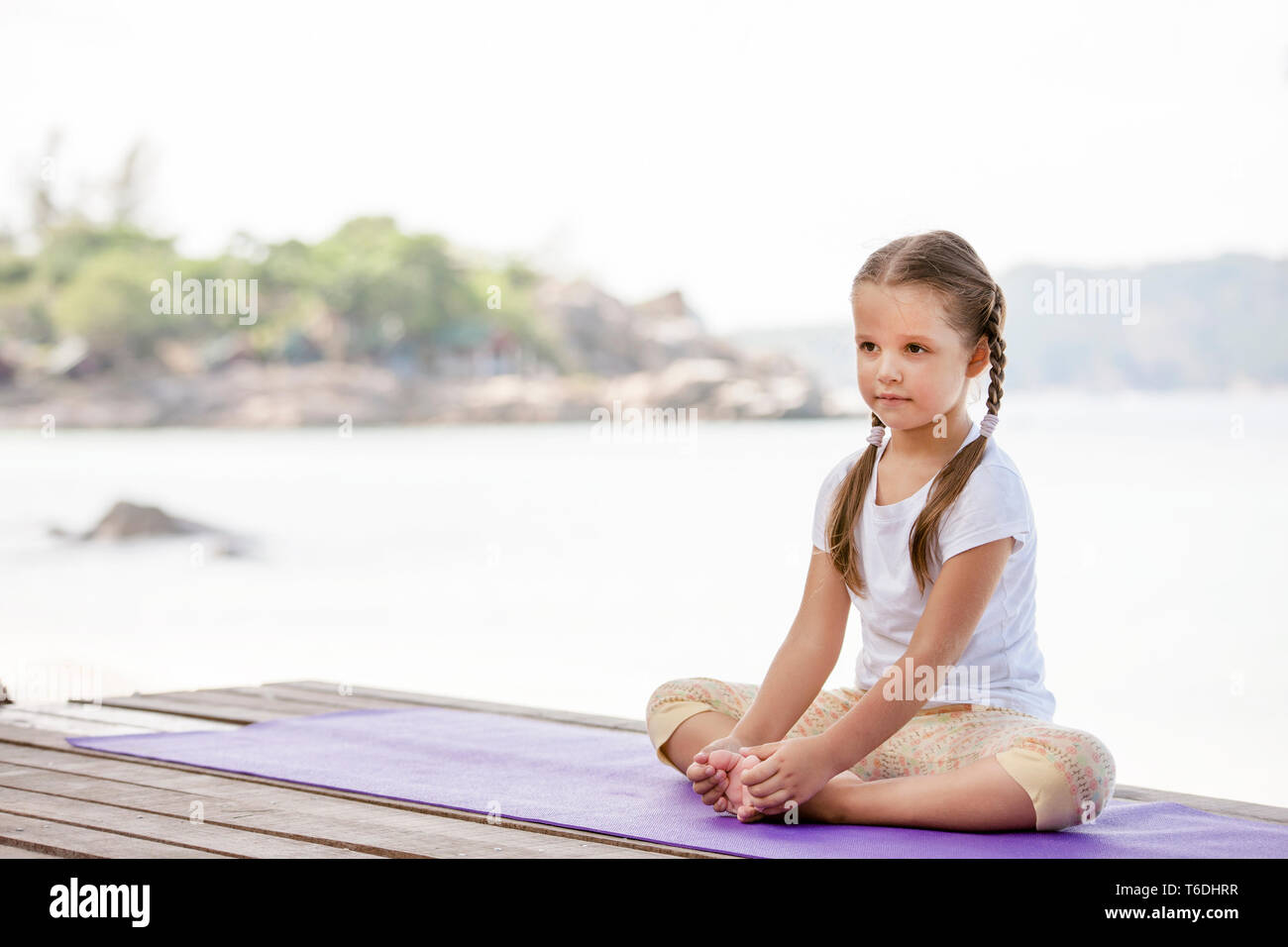 Child doing exercise on platform outdoors. Healthy lifestyle. Yoga girl - Stock Image