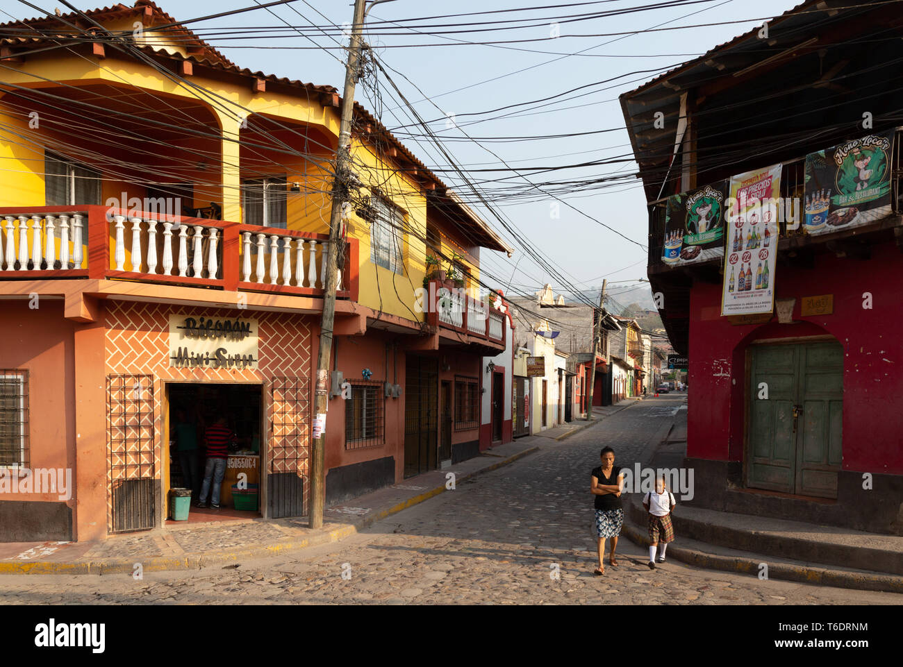 A mother walking her child to school - street scene in the  town of Copan Ruinas, Honduras, Central America - Stock Image