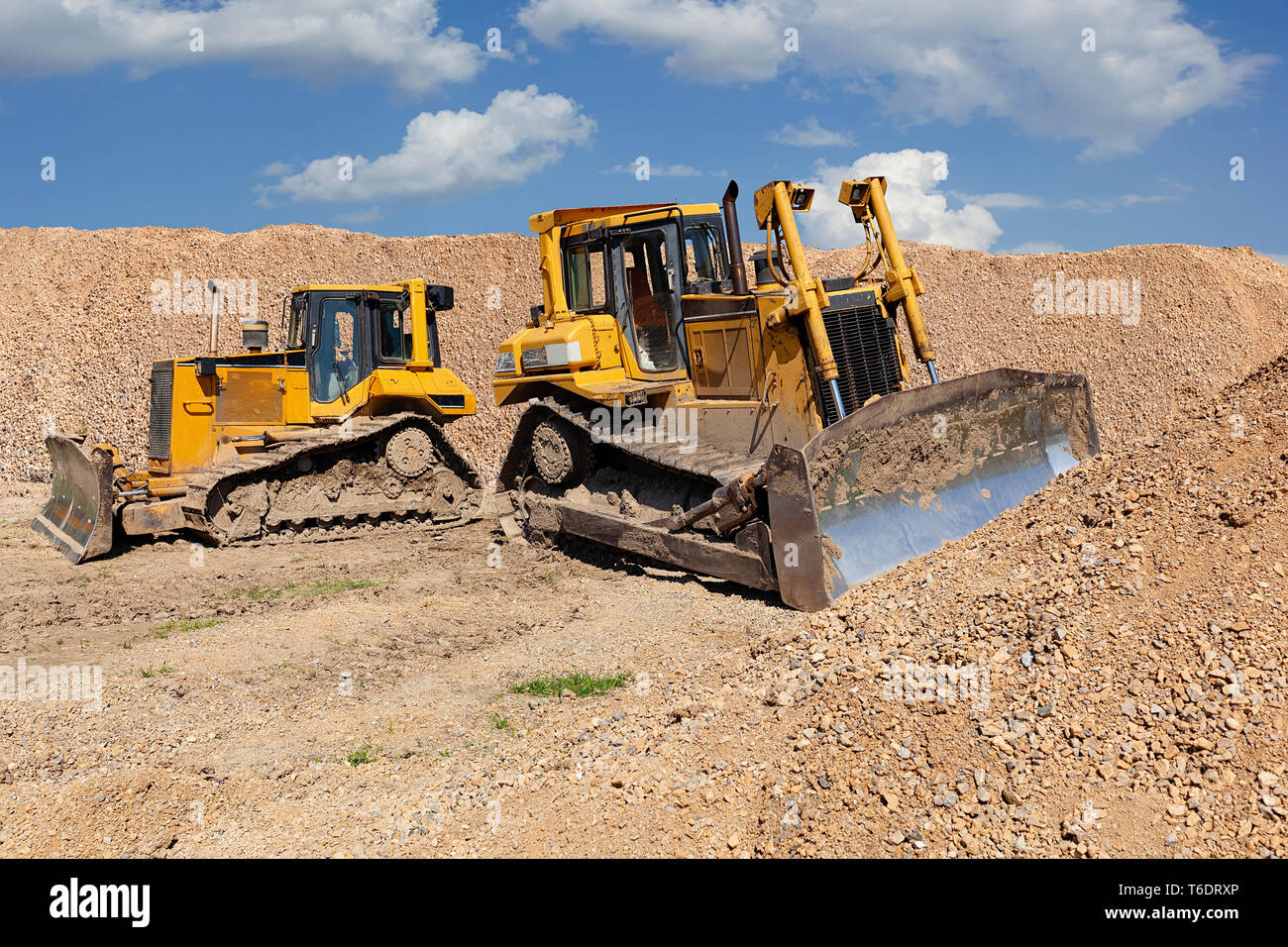 Two yellow dozers on a dirt terrain with blue sky with clouds in the background - Stock Image