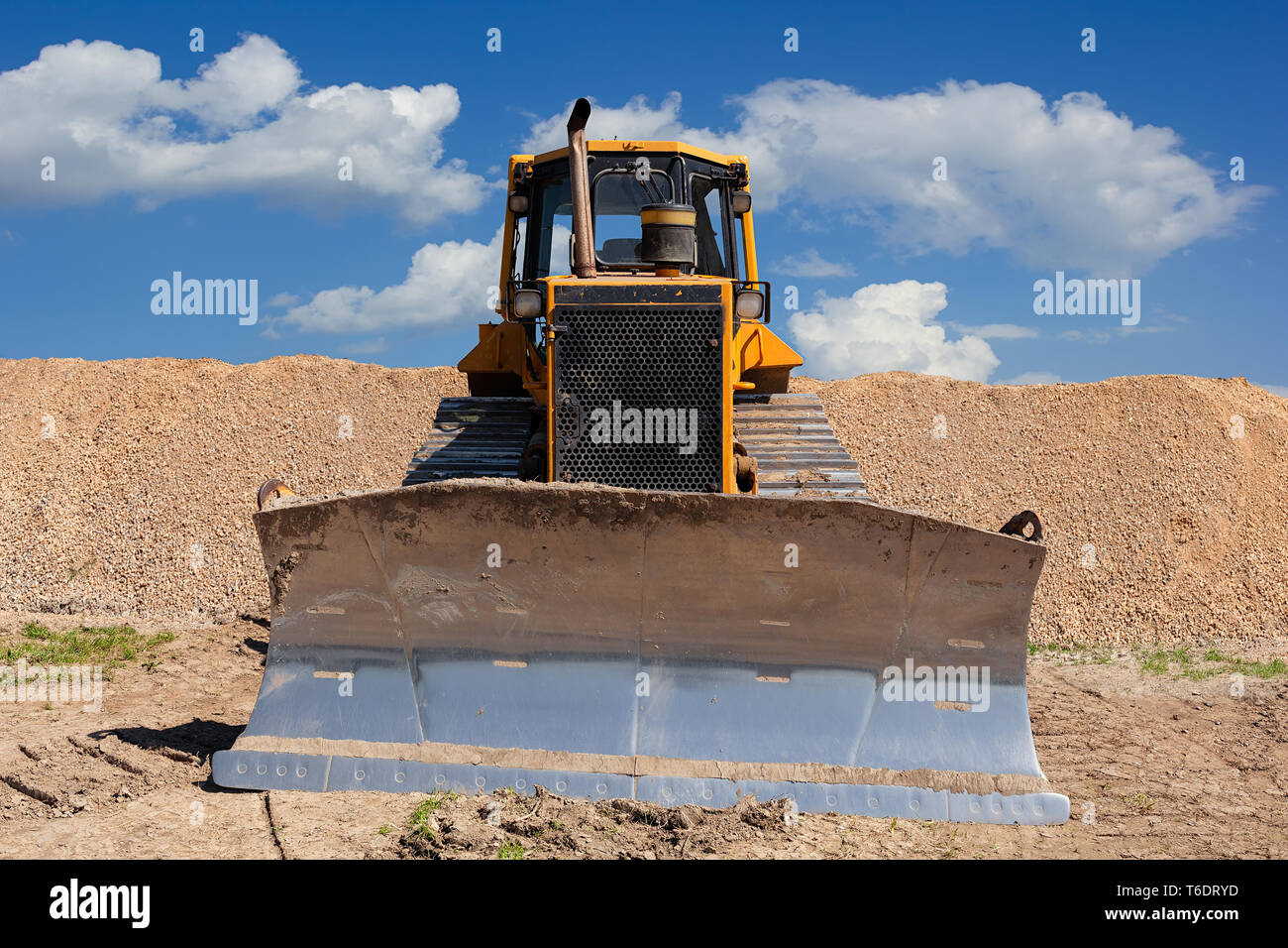 Yellow dozer on a dirt terrain with blue sky with clouds in the background - Stock Image