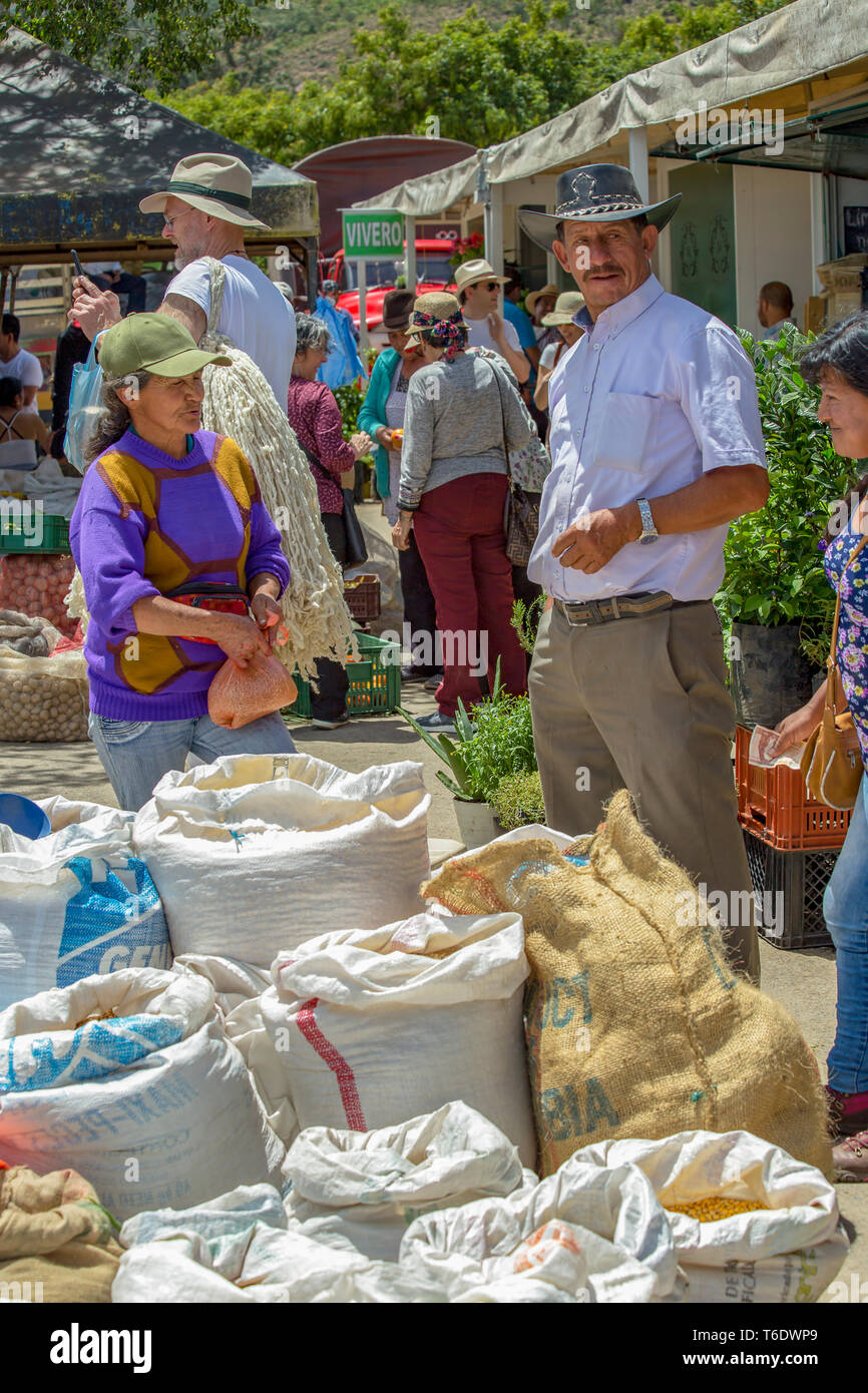 Villa de Leyva, Boyaca, Colombia - June 3, 2017: A man stands next to his sacks of grain while waits for customers at the traditional local market of  - Stock Image