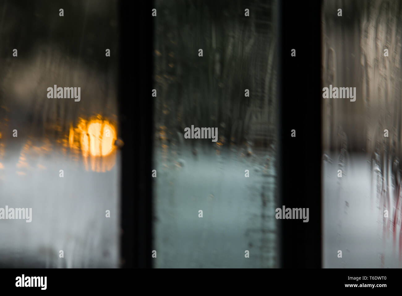 The rain rolls down the window of a coffee shop in Paris, France. A street light illuminating the window - Stock Image