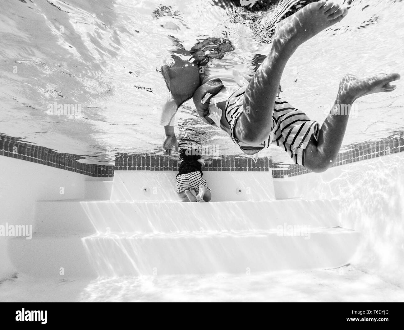 Black and white shot of a person swimming in a pool - Stock Image