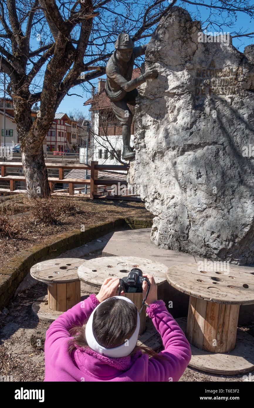 Woman photographing a Bronze statue that commemorates the ski guides of the Fassa valley a trhe village of Campitello - Stock Image