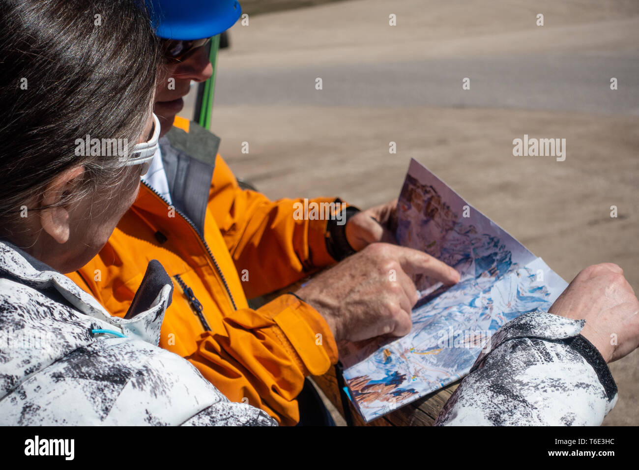 Two skiers looking at a piste map - Stock Image