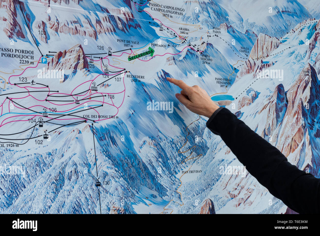 A hand is pointing to  a ski route on a street piste map in the dolomites ski area - Stock Image