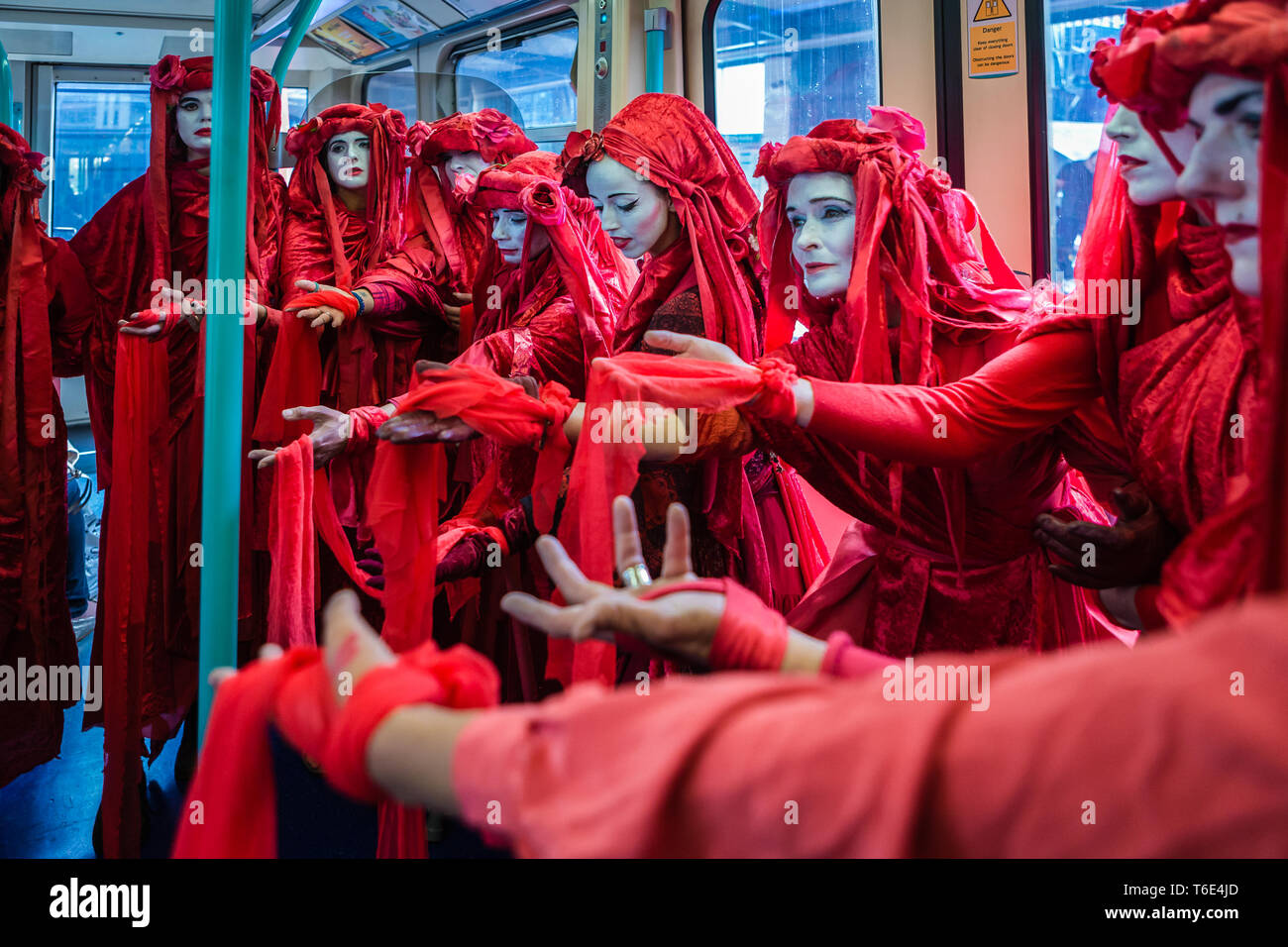Red Brigade of Extinction Rebellion ride the subway. - Stock Image