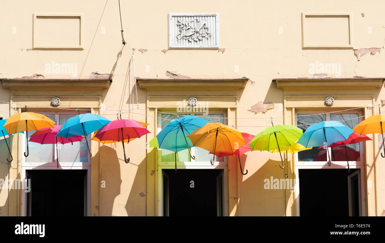 Colorful umbrellas hang in the sun on a leash - Stock Image