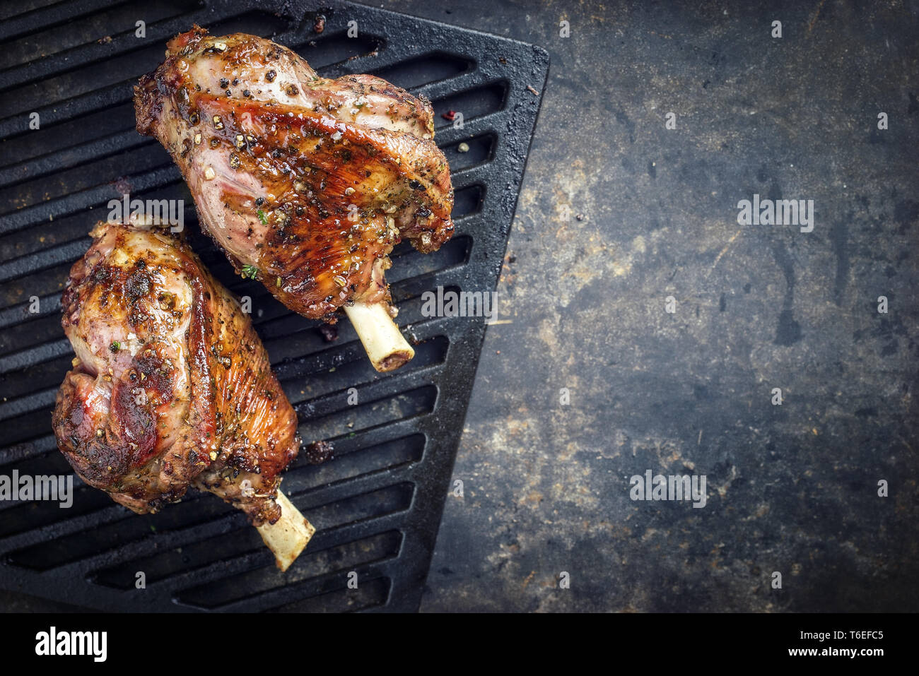 Two Barbecue Leg of Lamb as top view on cast iron grillage - Stock Image