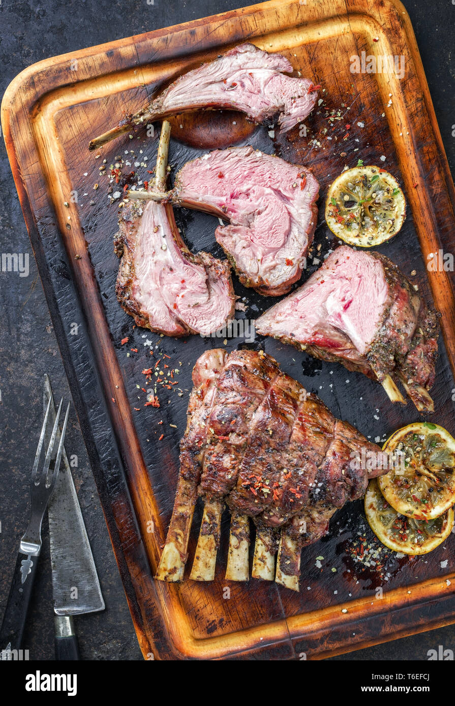 Barbecue Leg of Lamb and Rack as top view on burnt cutting board - Stock Image