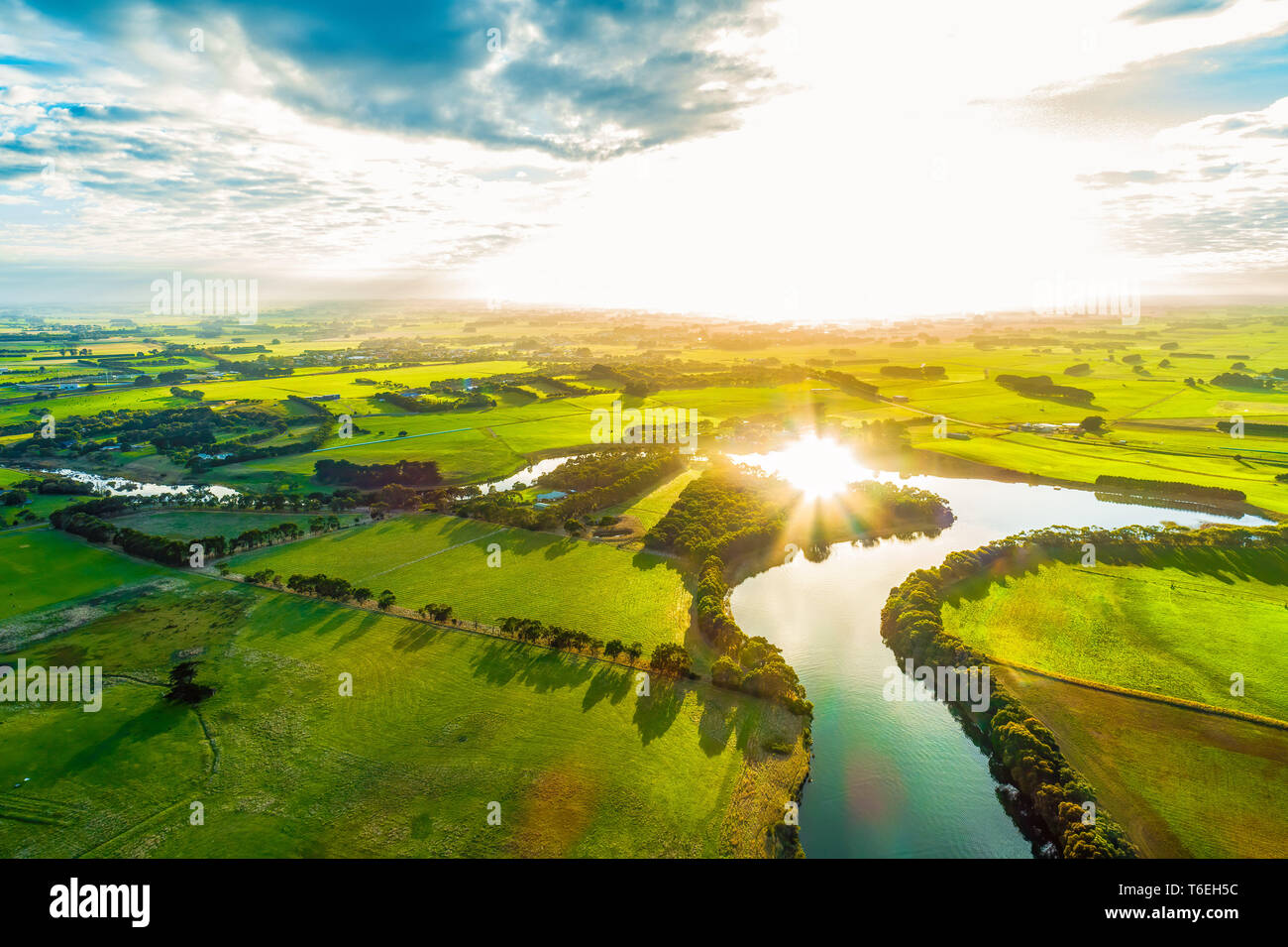 Bright sunset over scenic river in lush green countryside Stock Photo