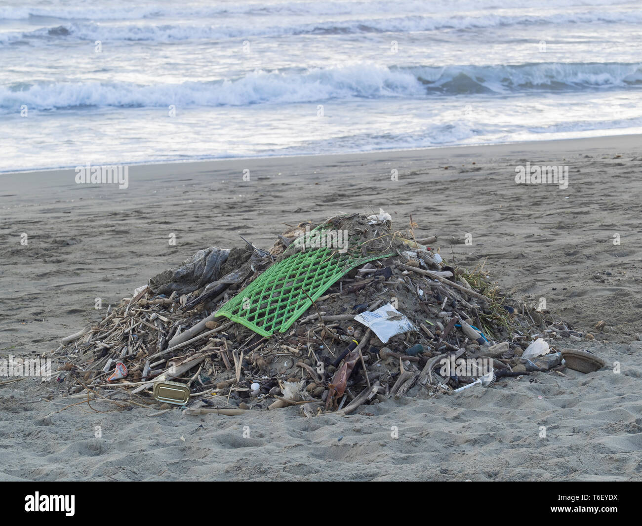 ocean pollution: waste collected on a sandy  beach: lots of objects mostly made of plastic mixed with natural residues - Stock Image