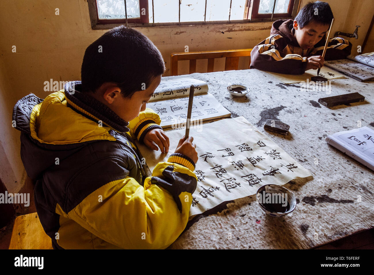 Lijiang, Yunnan province, China : Children practice at a traditional calligraphy school in the Old Town of Lijiang, a national historical and cultural - Stock Image