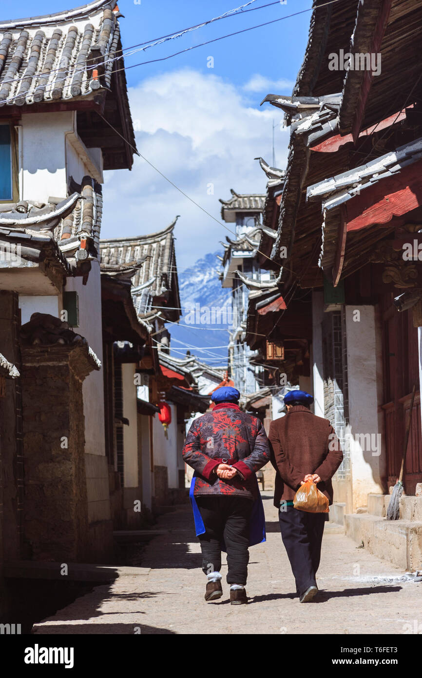 Lijiang, Yunnan province, China : Two women walk past traditional Naxi architecture in the Old Town of Lijiang, a national historical and cultural cit Stock Photo