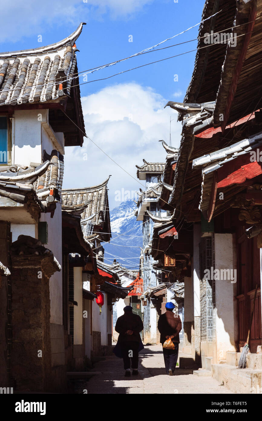 Lijiang, Yunnan province, China : Two women walk past traditional Naxi architecture in the Old Town of Lijiang, a national historical and cultural cit - Stock Image