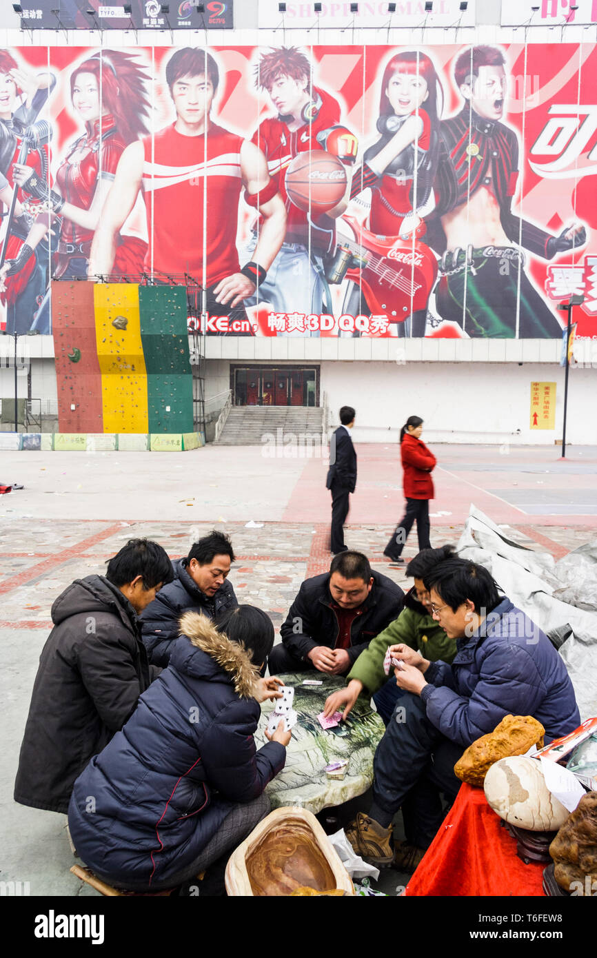 Chengdu, Sichuan province, China : Chinese men play a cards game in front of a big advertising billboard. - Stock Image