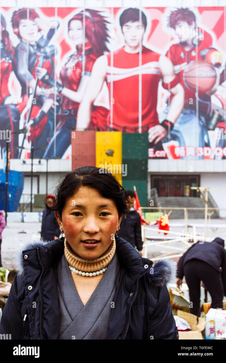 Chengdu, Sichuan province, China : A Tibetan woman poses for a portrait in front of a big advertising billboard. - Stock Image