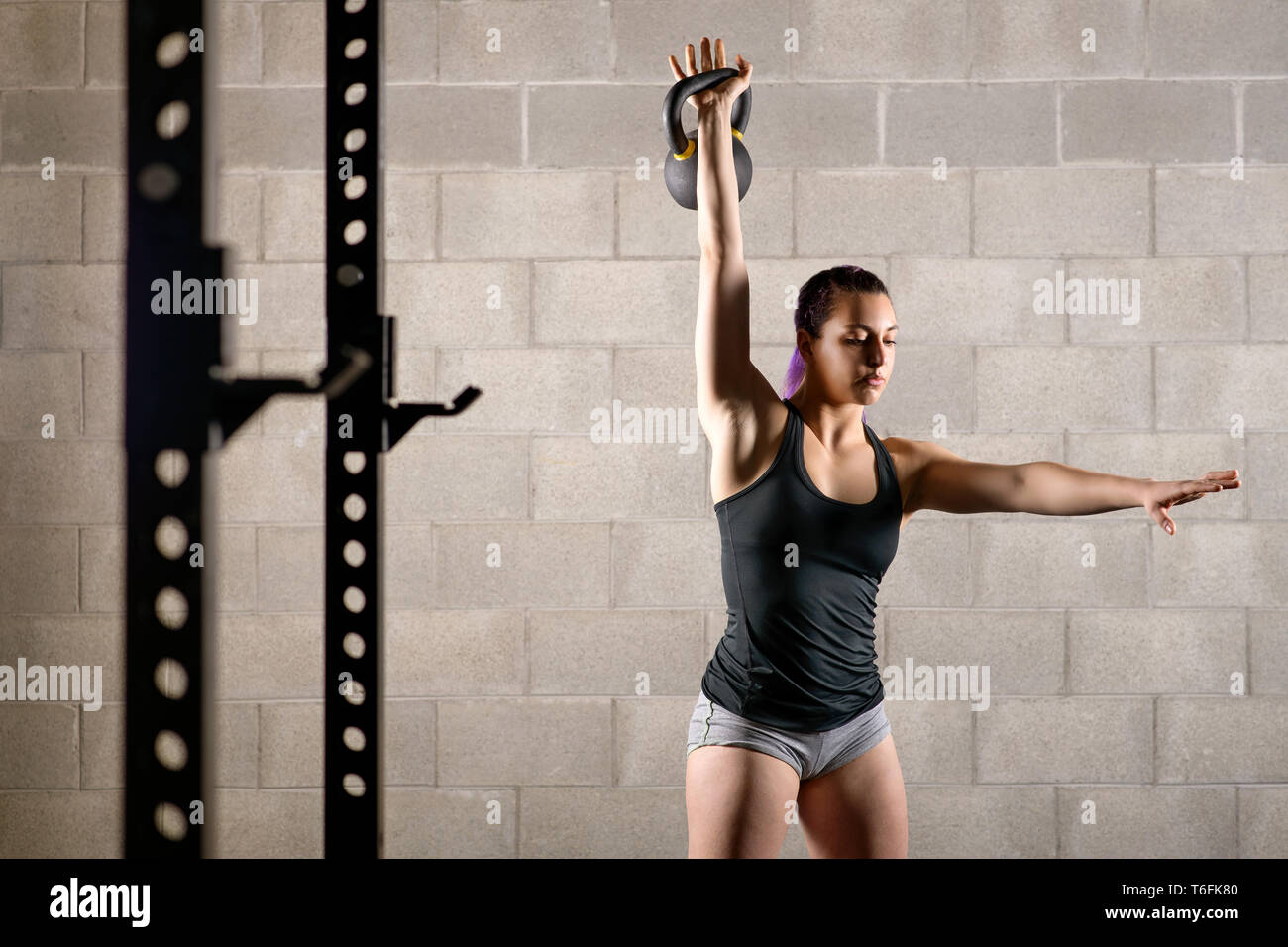 Muscular strong young woman working out in a gym with a kettlebell weight raising it with extended arm in a health and fitness concept - Stock Image