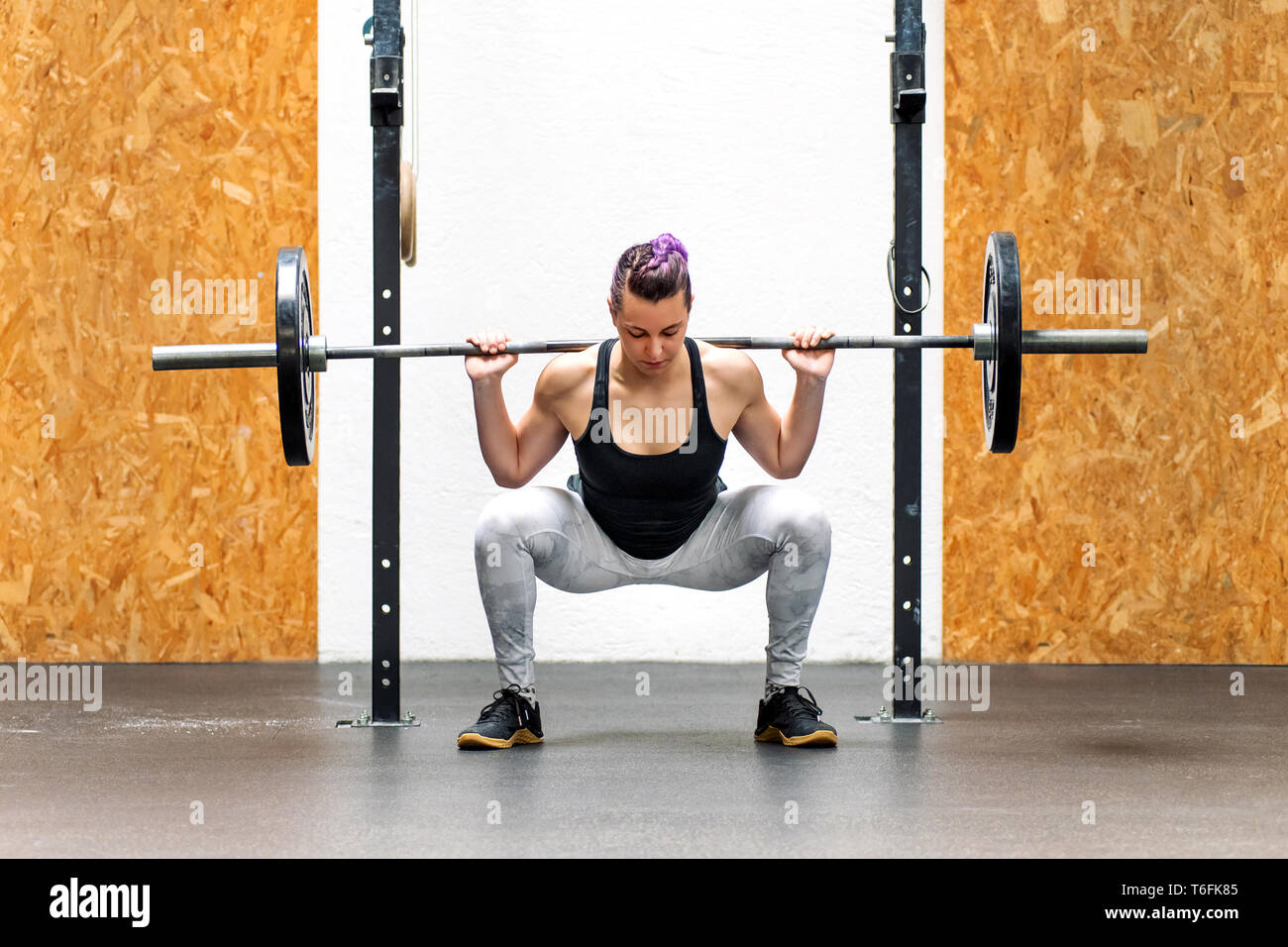 Young girl doing a back squat with a barbell weight resting across the back of her shoulders in a gym - Stock Image