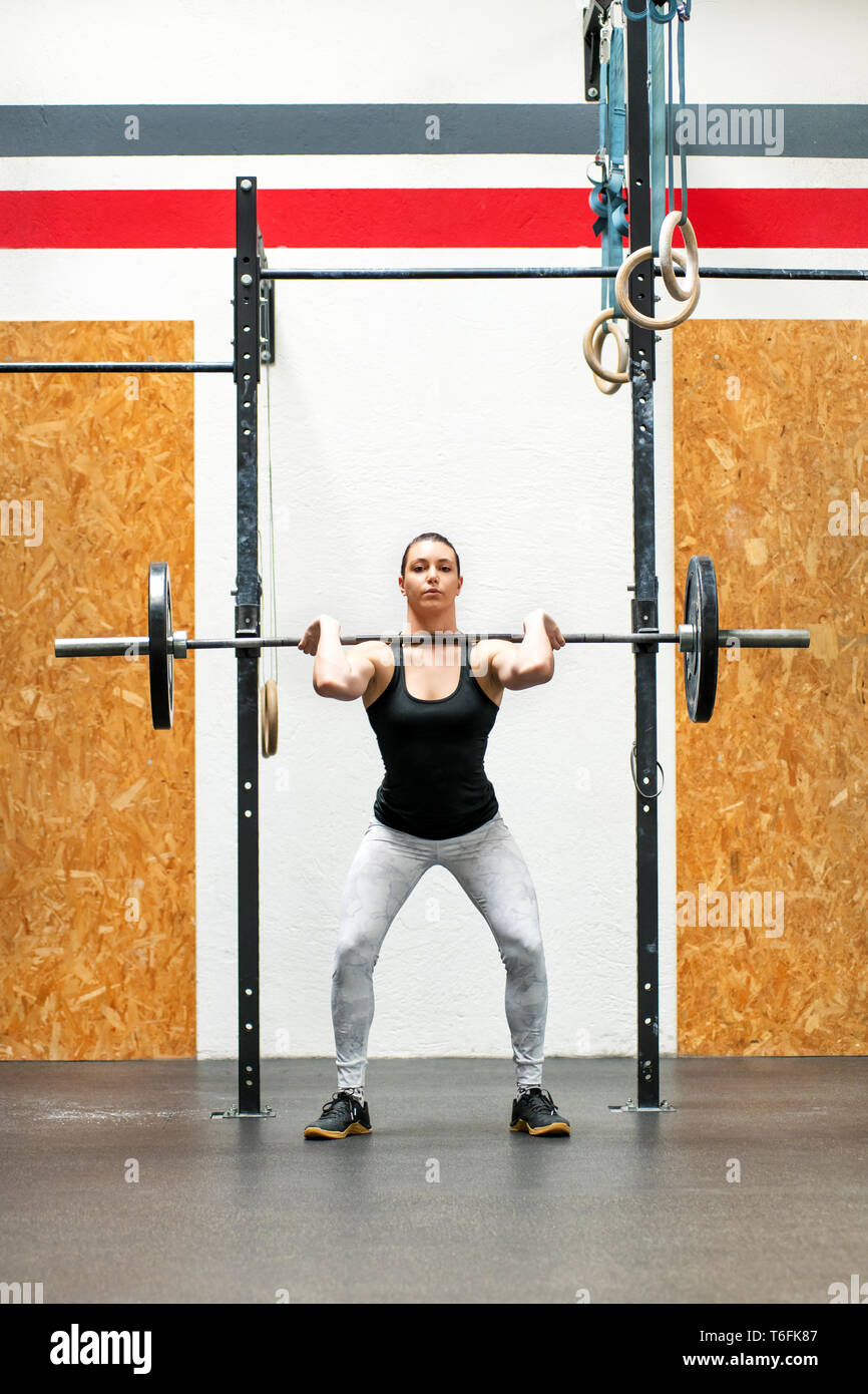 Young woman body builder or athlete doing a front squat in a gym raising the barbell to her shoulders in the upright position to strengthen her muscle - Stock Image
