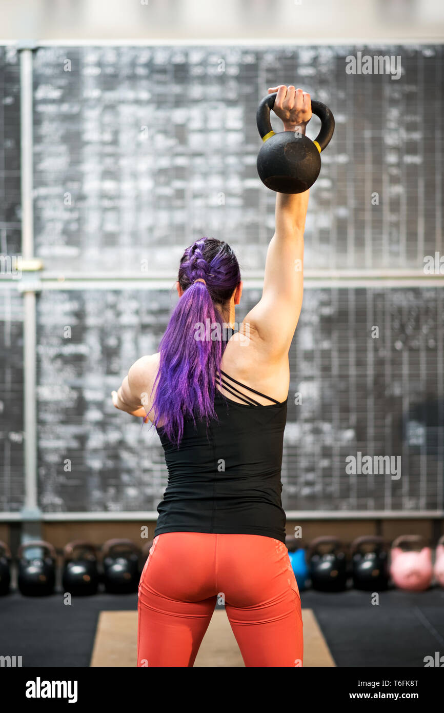 Rear view of a muscular young woman swinging a kettlebell weight and holding it above her head with one hand during training inside a gym Stock Photo