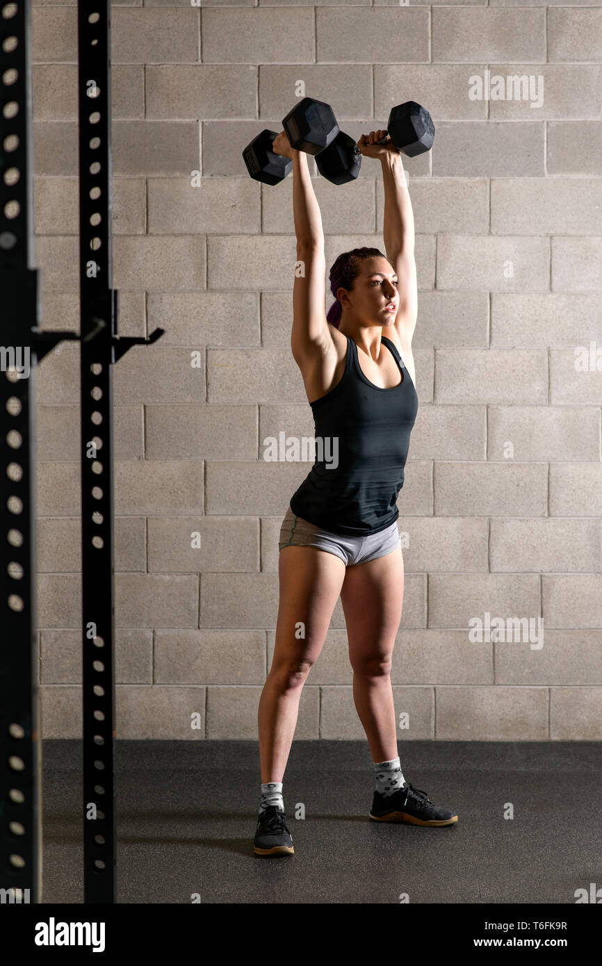 Fit strong young woman doing weightlifting exercises raising a pair of dumbbells above her head inside a gymnasium - Stock Image