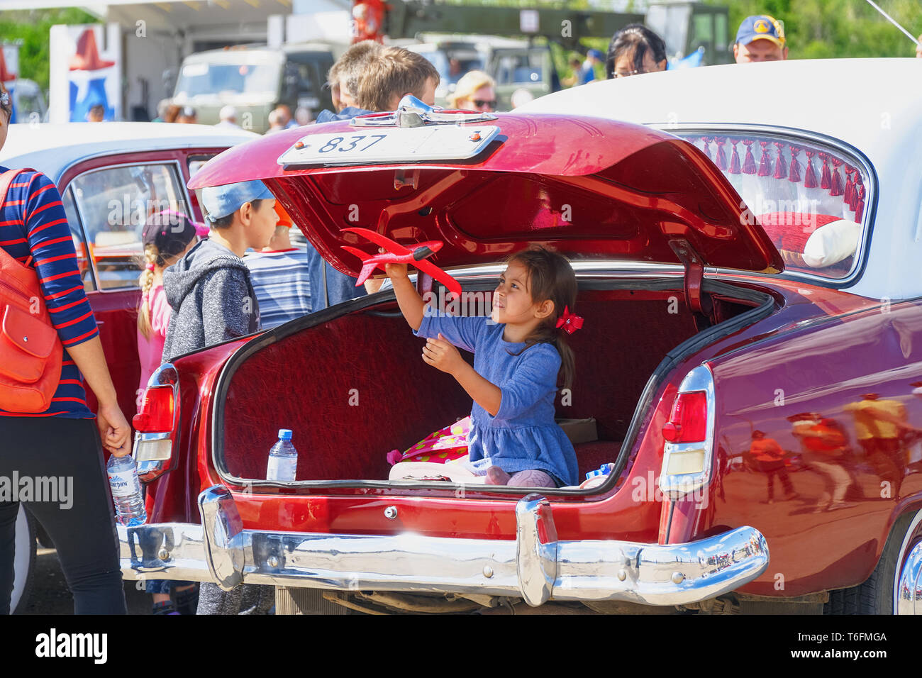 Girl plays sitting in the trunk of a car - Stock Image