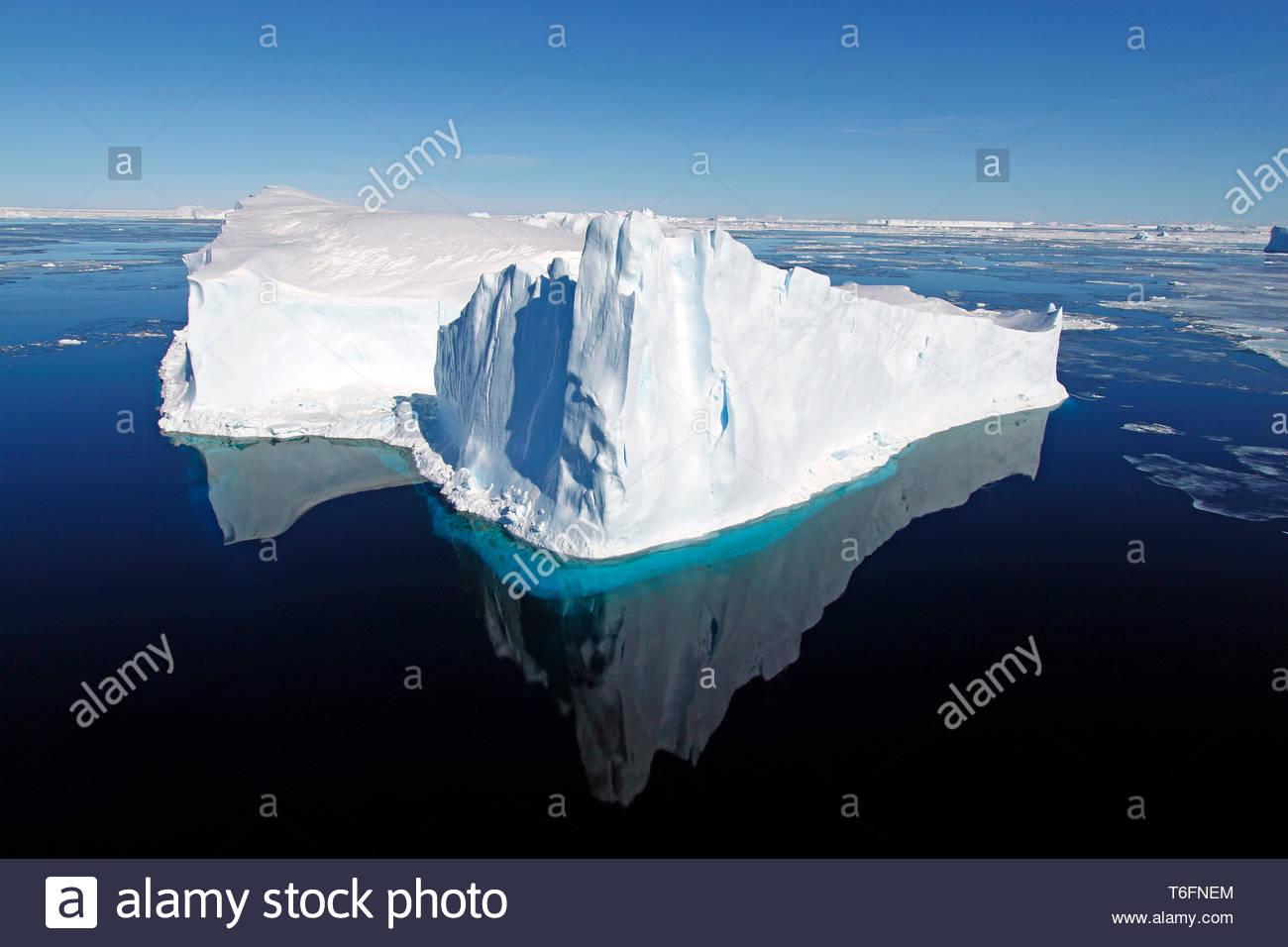 Treibender Eisberg spiegelt sich im tiefblauen Wasser, Antarktis | Drifting iceberg, mirroring in water, Antarctic - Stock Image