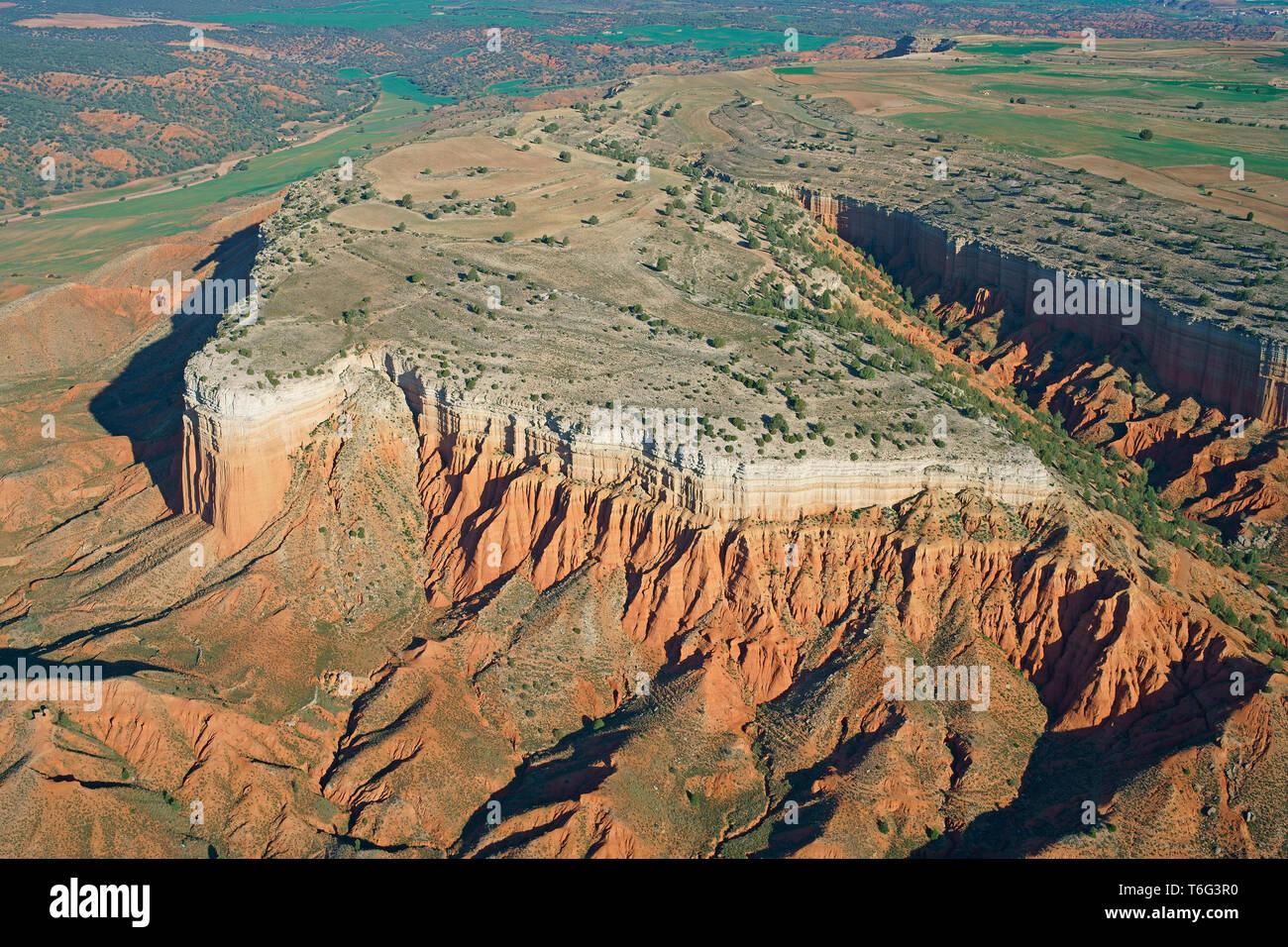 SEMI-ARID MESA WITH ITS CLIFF OF MULTICOLORED STRATA (aerial view). Cañon Rojo (also known as Rambla de Barrachina), Teruel, Aragon, Spain. - Stock Image