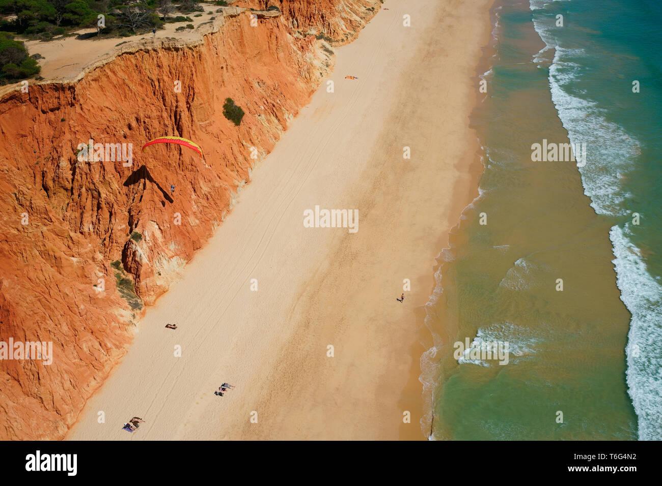 PARAGLIDER USING THE SEA BREEZE TO SOAR ALONGSIDE A COLORFUL SEASIDE CLIFF (aerial view). Praia da Falésia, Albufeira, Algarve, Portugal. Stock Photo