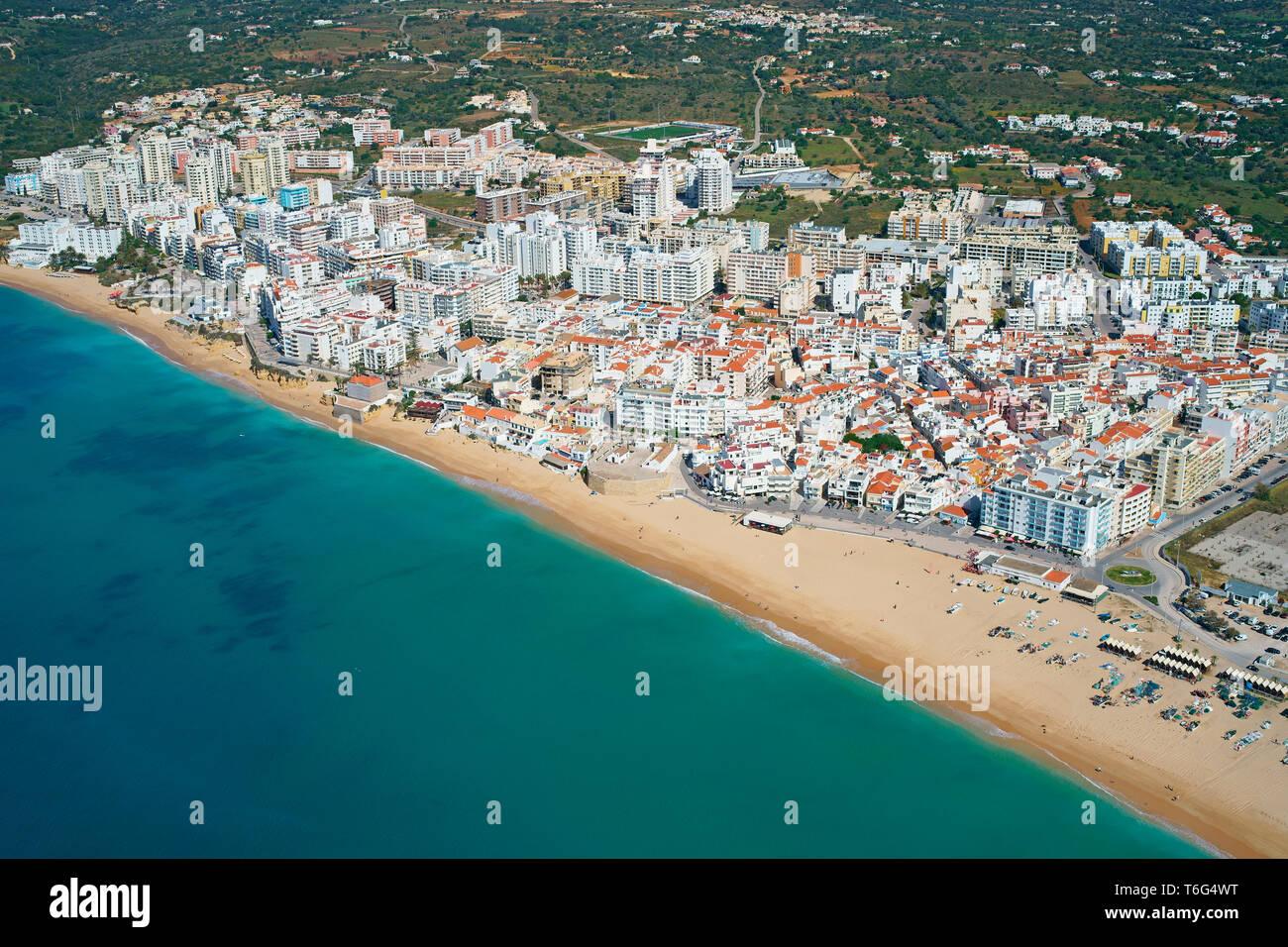 FISHING VILLAGE AND TOURIST CENTER NEAR THE MAJOR SEASIDE ROCK FORMATIONS OF THE ALGARVE (aerial view). Armação de Pêra, Portugal. - Stock Image