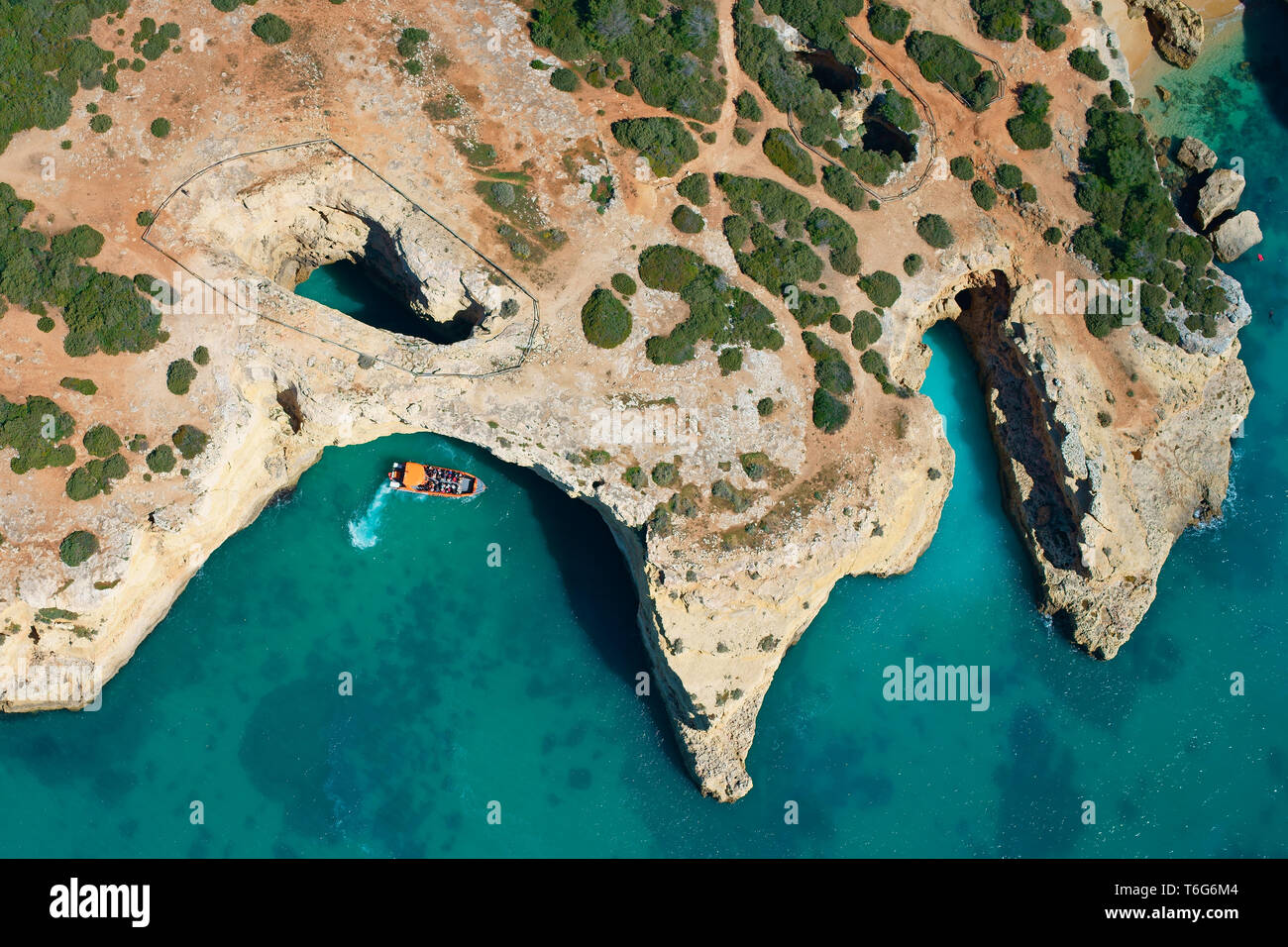 SIGHTSEEING BOAT APPROACHING A SEA CAVE / SINKHOLE ON A ROCKY SHORELINE NEAR ALBANDEIRA BEACH (aerial view). Lagoa, Algarve, Portugal. - Stock Image