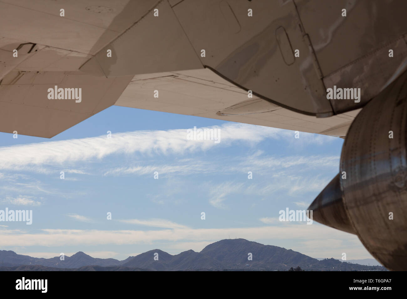 Spectacular view of an aircraft, closeup.Blue sky, mountains, day time. - Stock Image
