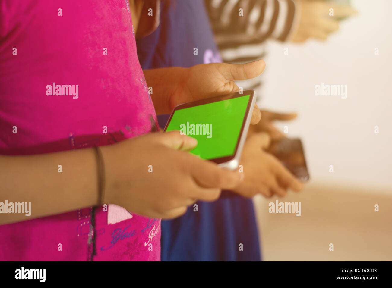 Social media addiction, Closeup of kids hand using the smartphone with greenscreen. - Stock Image