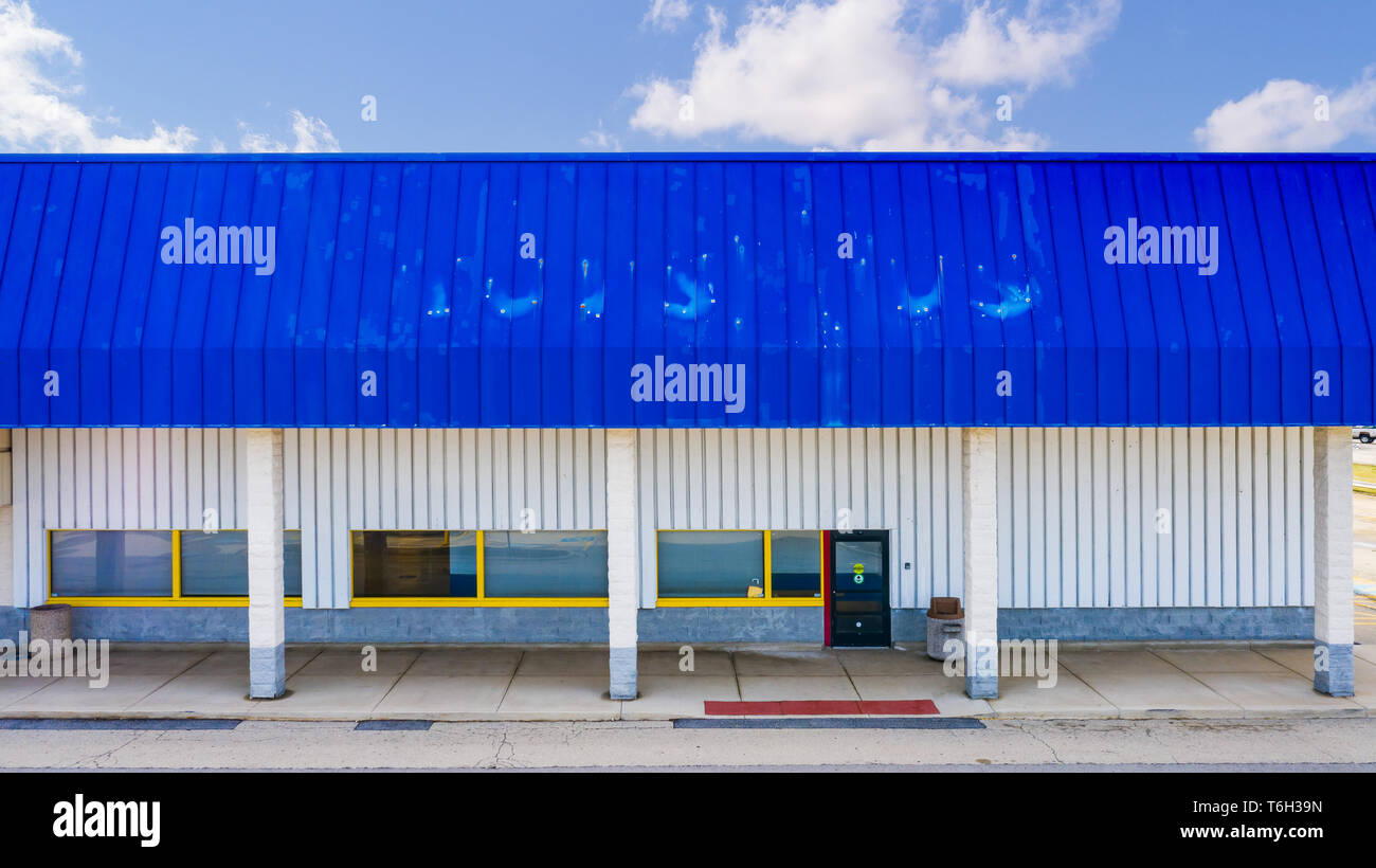 An empty shell of a Toys R Us store after declaring bankruptcy. The remnants of the old sign are still lingering on the building. - Stock Image