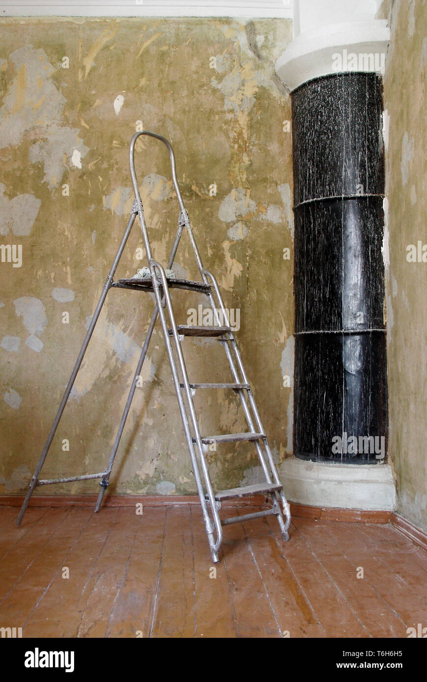 a ladder in the room during the repair with shabby wall and black stove in the corner - Stock Image