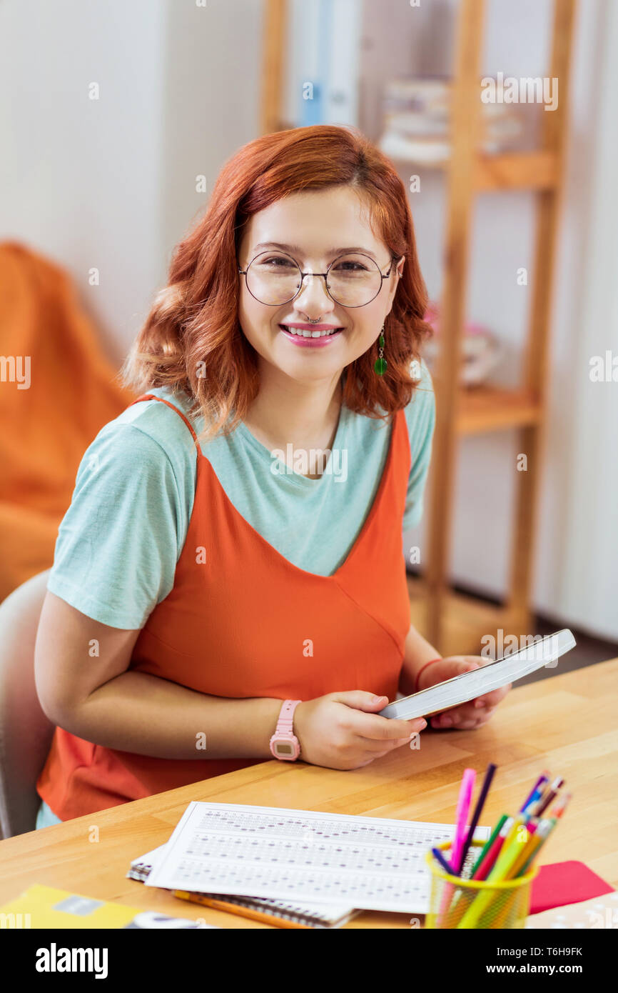 Delighted smart young woman holding her manuals - Stock Image
