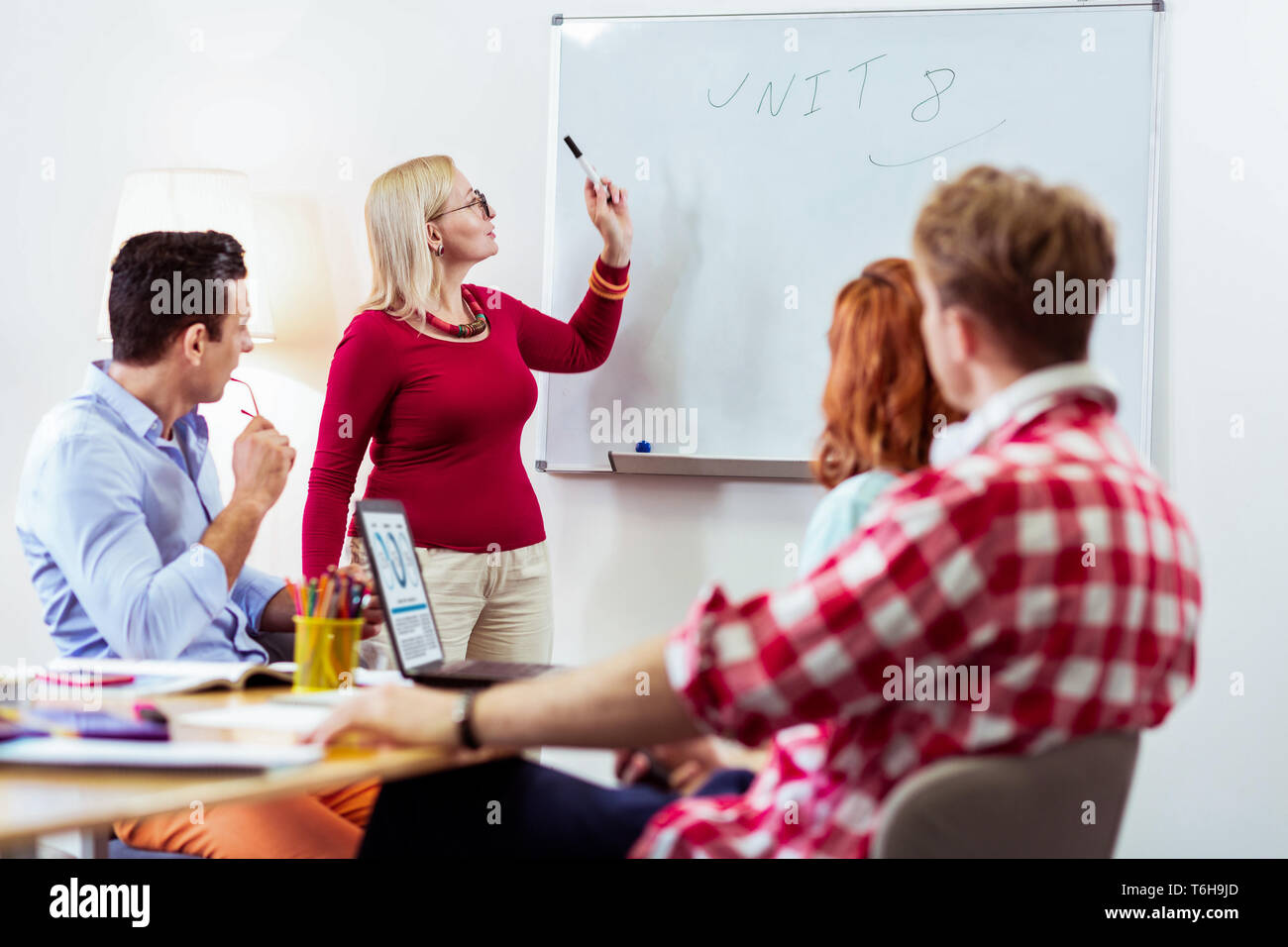 Nice pleasant woman pointing at the whiteboard - Stock Image