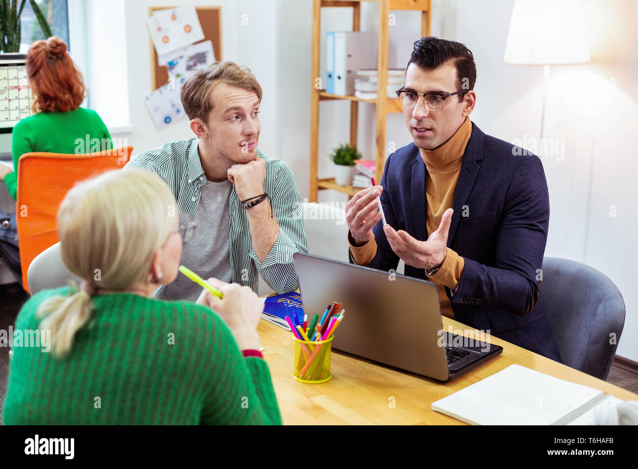 Serious nice young man talking about work - Stock Image