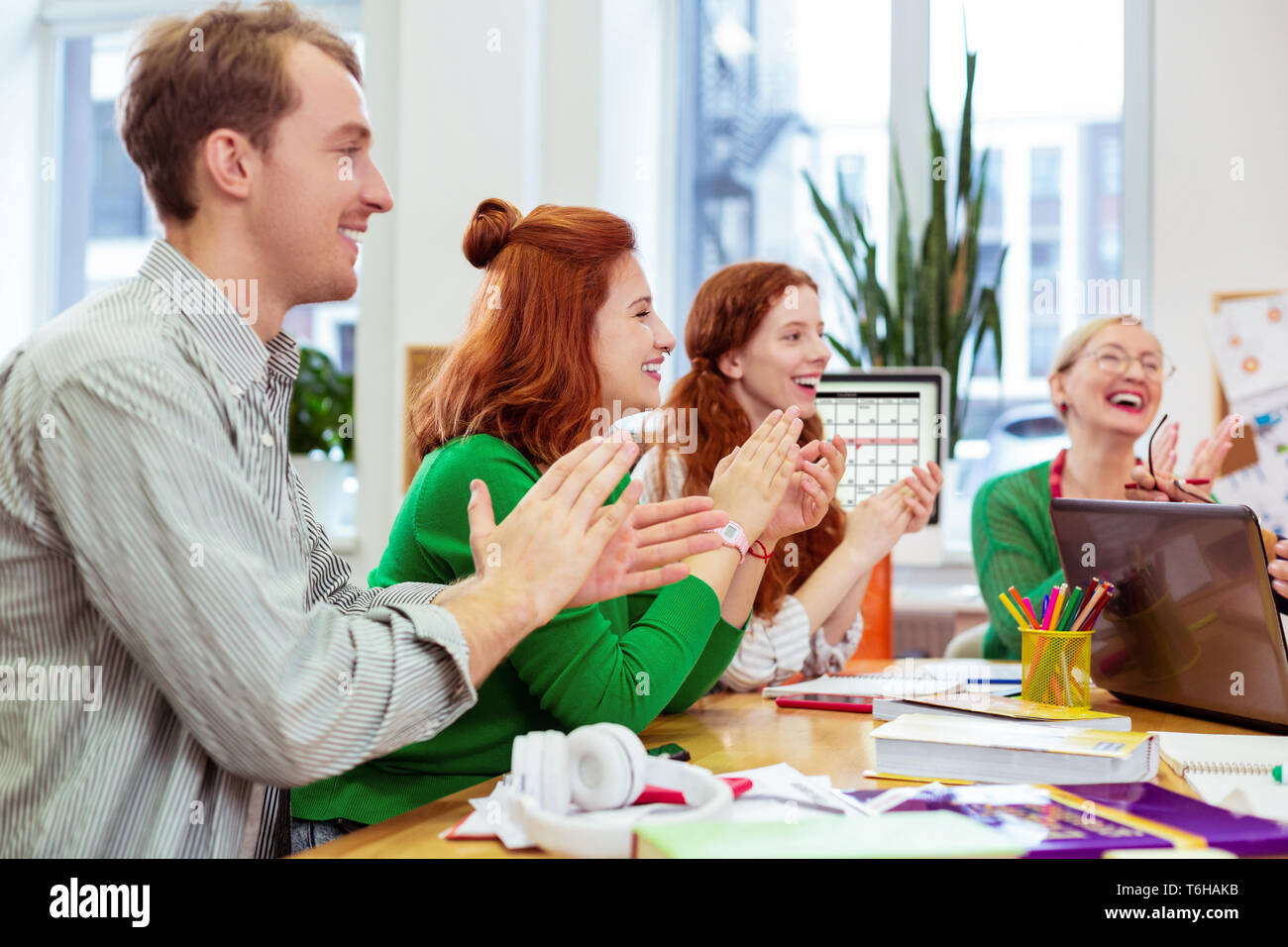Delighted happy people showing their approval with applause - Stock Image