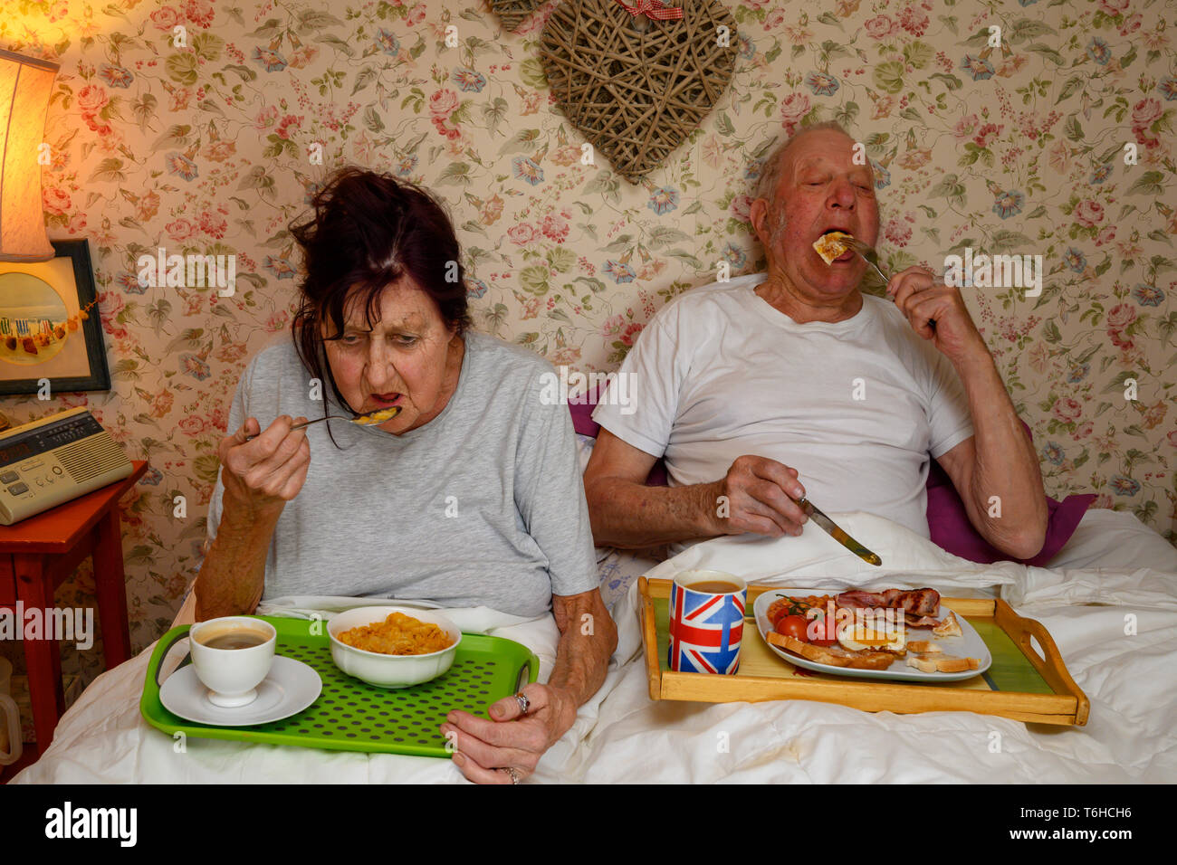 Elderly couple eating breakfast in bed - Stock Image