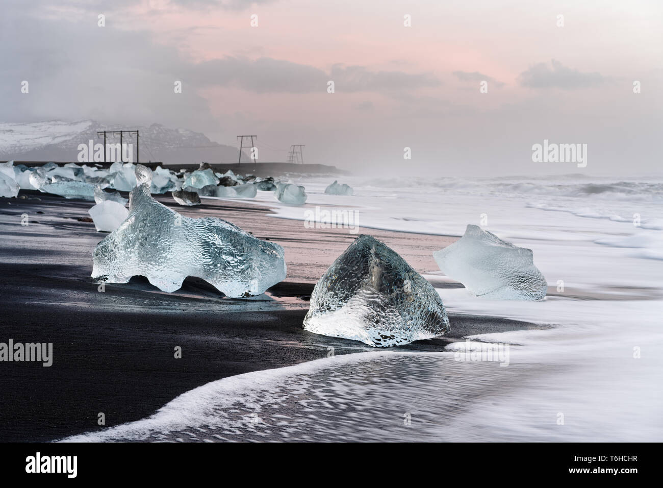 Ice blocks are picturesquely located on a black volcanic beach, the movement of the waves can be seen (long time exposure), above it a cloudy sky with - Stock Image
