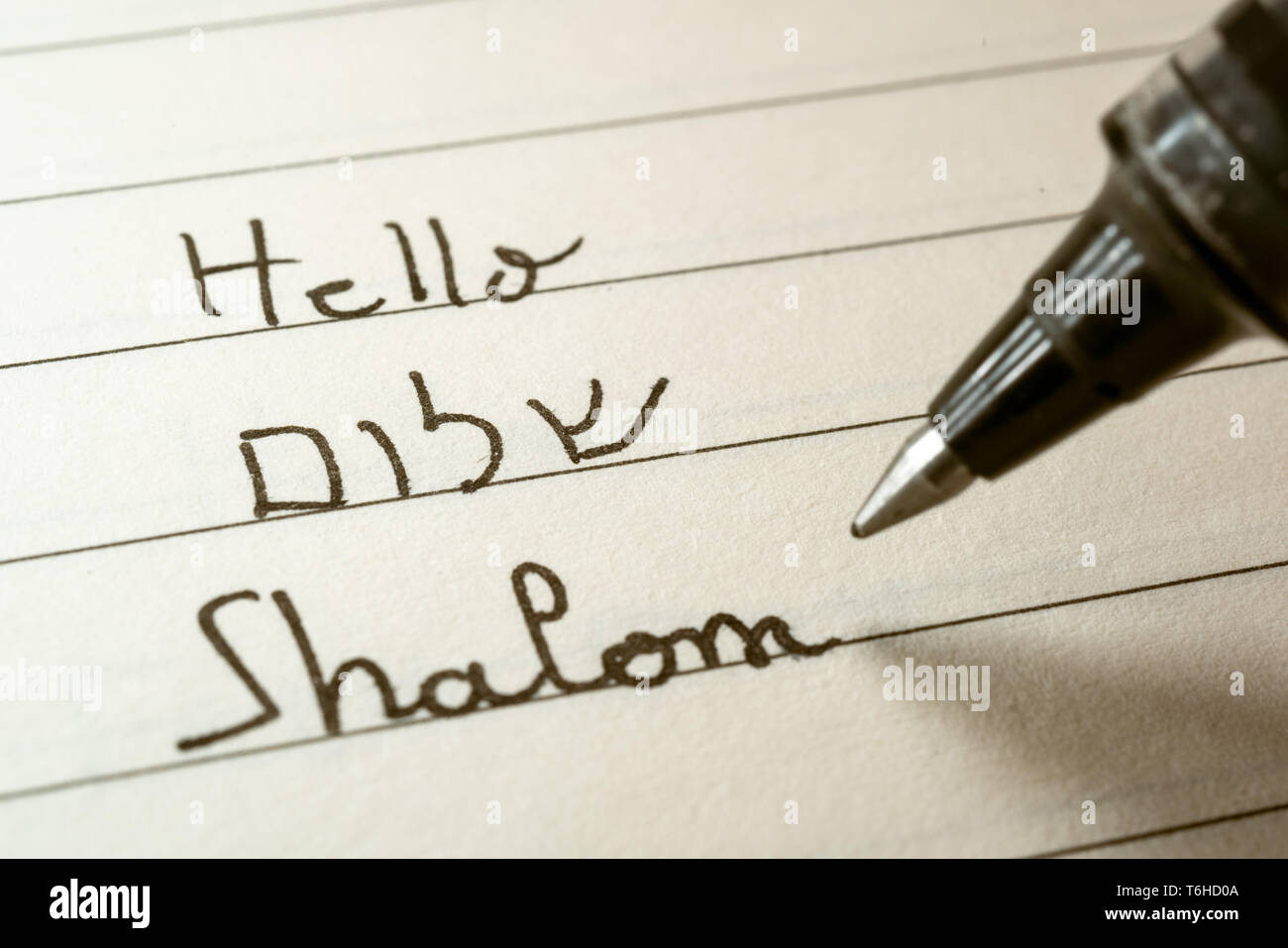 Beginner Hebrew language learner writing Hello Shalom word in Hebrew alphabet on a notebook close-up shot - Stock Image