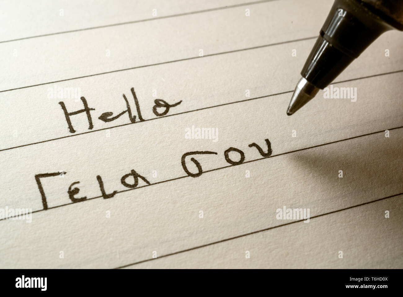 Beginner Greek language learner writing Hello word in greek alphabet on a notebook close-up shot - Stock Image