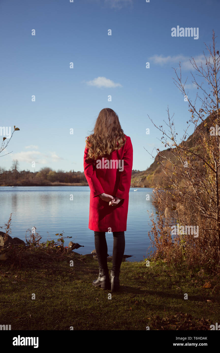 Young woman gazing out over Duddingston Loch in Edinburgh - Stock Image