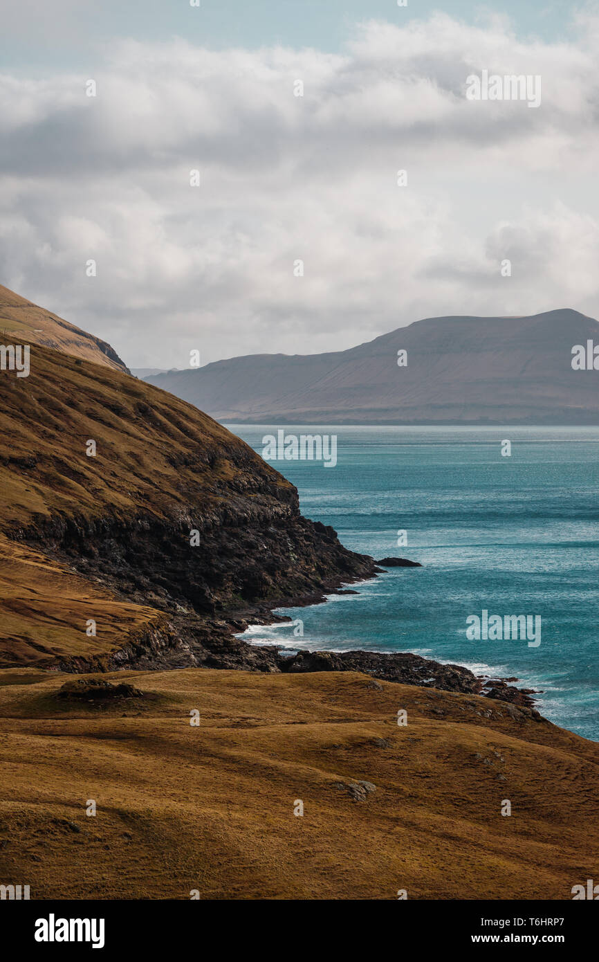 Coastal cliffs with turquoise Atlantic water near the small village of Norðradalur on a windy spring afternoon (Faroe Islands, Denmark, Europe) - Stock Image
