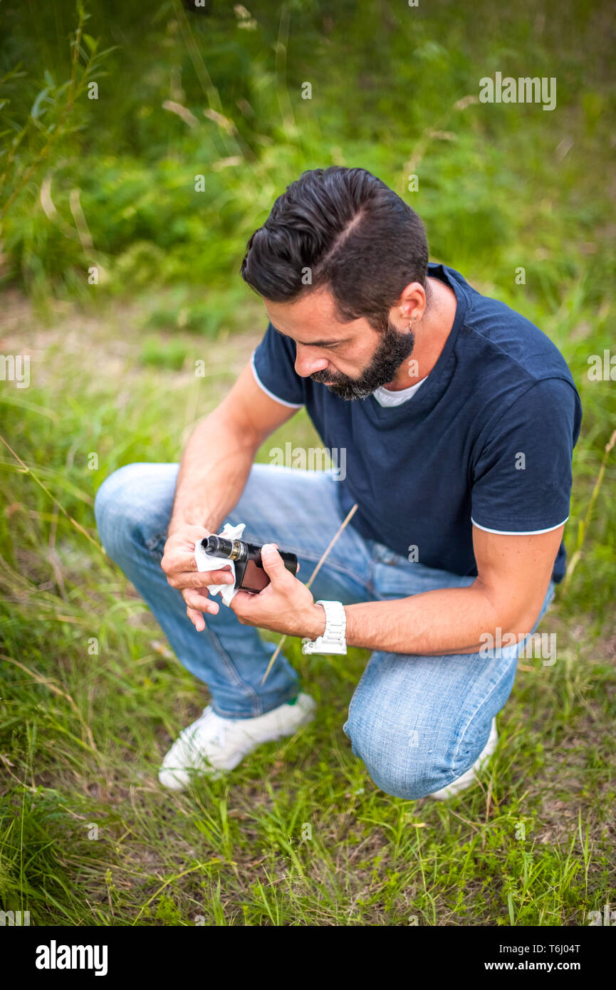 A bearded man in nature prepares an electronic cigarette for use - Stock Image