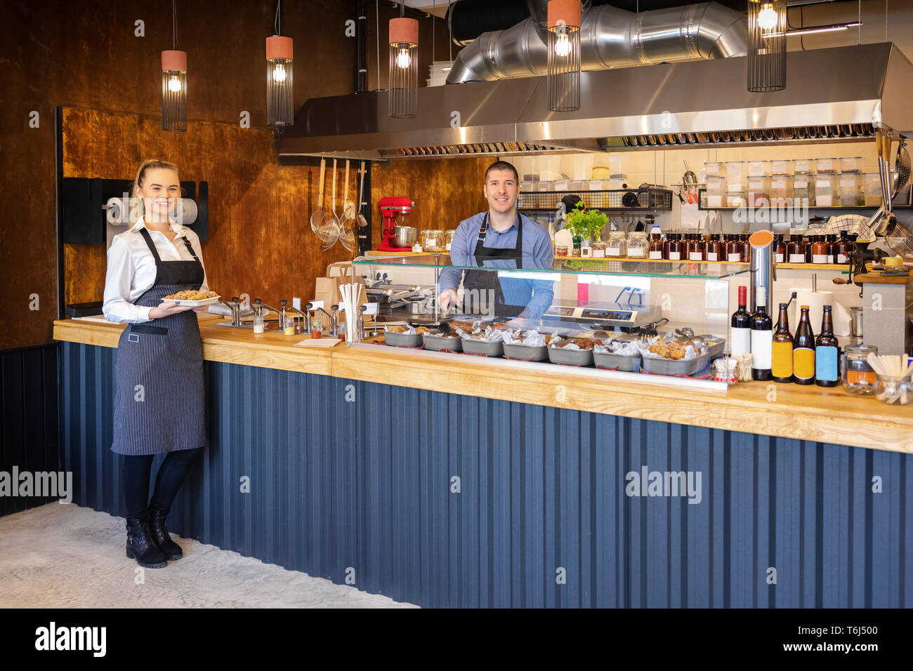 Counter service at modern bistro with smiling waiters serving food – happy business owners in small restaurant with open kitchen inviting people insid - Stock Image